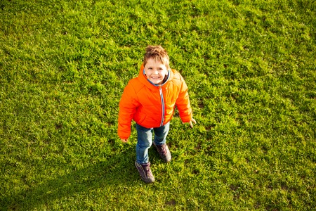 Happy boy standing on green grass lawn in spring