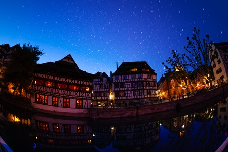 Traditional French buildings along the Ill river embankment against starry sky, Strasbourg