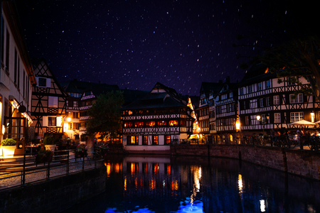 Traditional French buildings along the Ill river embankment on the starry sky background, Strasbourg