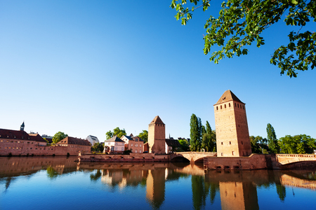 Beautiful view of Grande Ile island with its towers and covered bridges reflected in Ill river water at sunny day, Strasbourg, France