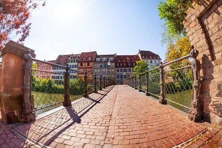 Empty bridge paved of bricks across the Ill river in Strasbourg, France