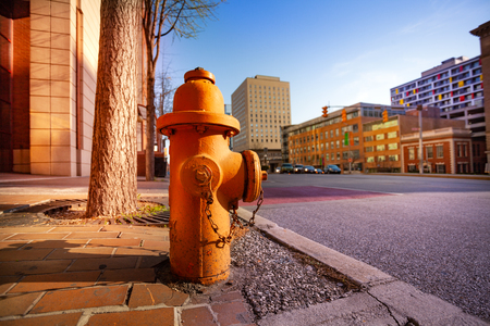 Close-up picture of orange fire hydrant on the sidewalk of Baltimore city, Maryland, USA
