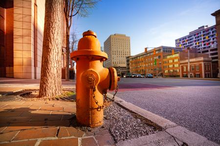 Nahaufnahme des orangefarbenen Hydranten auf dem Bürgersteig von Baltimore City, Maryland, USA Standard-Bild