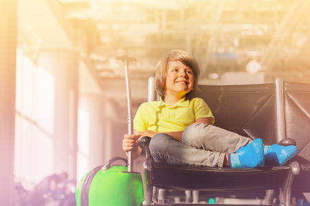 Boy sitting with trunk at airport departure lounge