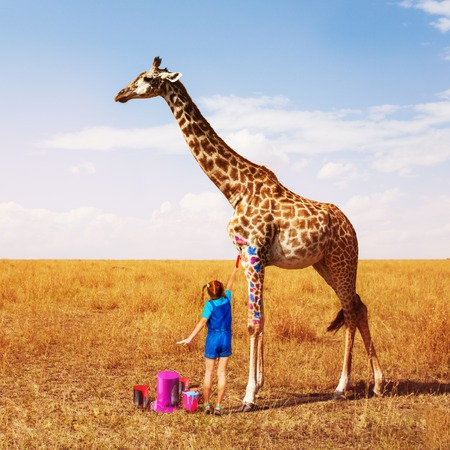 Little girl painting giraffe into many colors Stock Photo