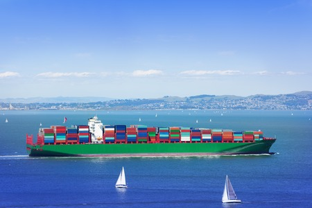 Full loaded cargo ship in sea among white yachts Stock Photo