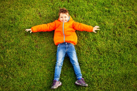 Happy little boy lying on green grass in park