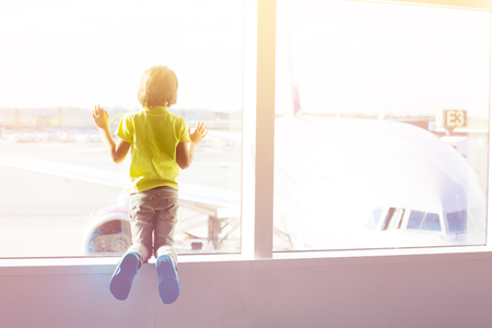 Boy looks on aircrafts through window of terminal