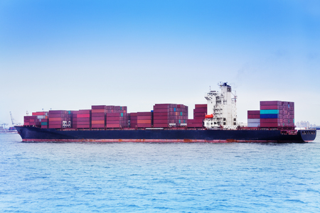 Ship full loaded with containers against blue sky Stock Photo