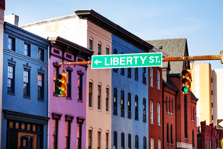 Guide sign at Baltimore street with colored houses Stock Photo