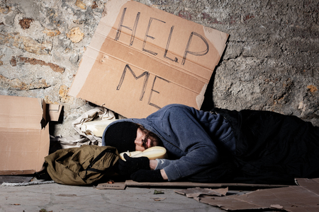 Beggar in tattered clothes sleeping at sidewalk Stock Photo
