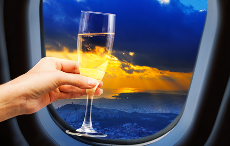 city view from plane window with champagne glass