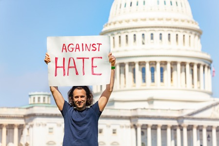 Protester holding sign against hate in his hands Imagens