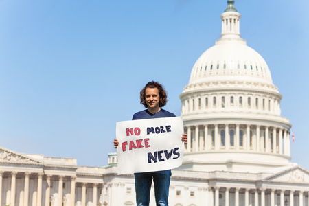 Protester holding sign saying no more fake news Imagens - 117618962