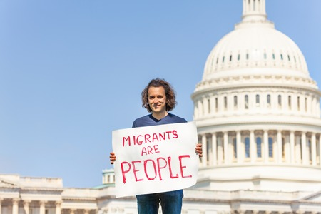 Protester holding sign migrants are people in hands Foto de archivo