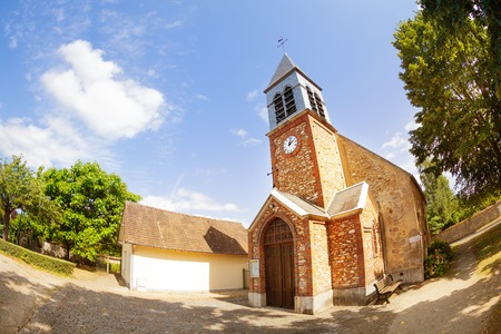 Old red brick chapel with clock tower in France