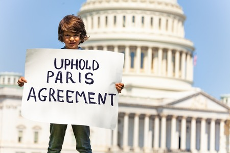 Protester holding sign uphold Paris agreement in hands Imagens