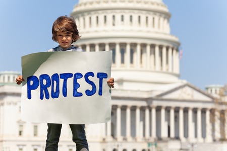 Boy manifesting holding sign saying protest in hands