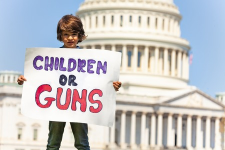 Protester holding sign children or guns in hands