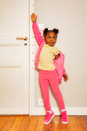 Little black girl try to be higher on door scale Stock Photo