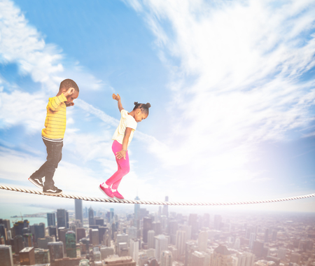 Two kids walking over the rope in modern city