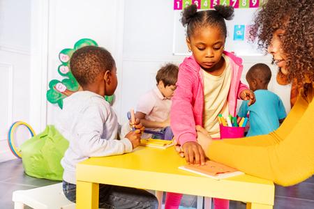 Kleuterklas kinderen knop met leraar Stockfoto