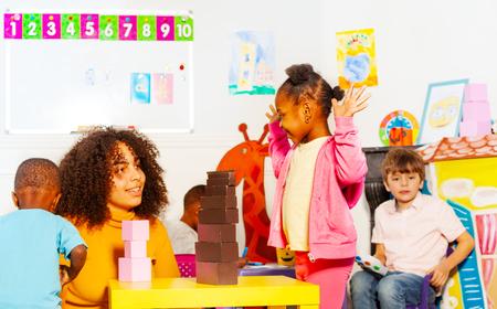 Happy girl play with teacher building blocks Фото со стока - 120180605