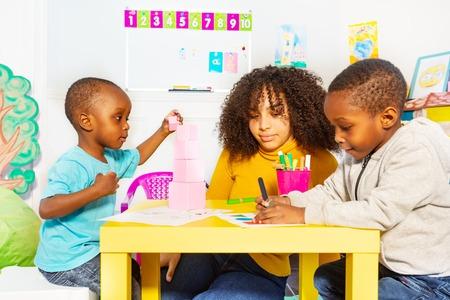 Small boys with teacher do nursery class exercises