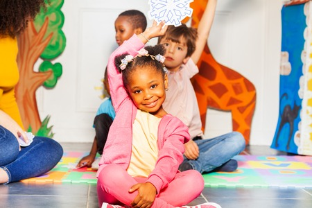 Little black girl sitting in the nursery group showing snowflake snow weather with card