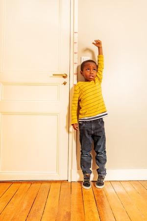 boy measuring his height benchmark on door at home Archivio Fotografico