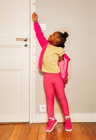 Kleines schwarzes Mädchen betrügt, um auf der Türskala hoch auszusehen Standard-Bild