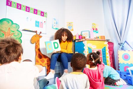 Les enfants s'assoient autour du professeur et apprennent l'alphabet Banque d'images