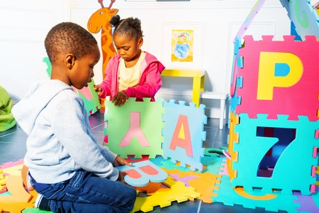 Black boy and girl build with letter. number block