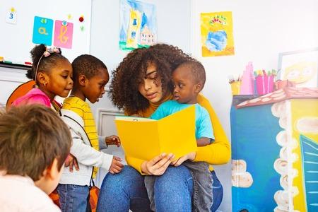 Eine Gruppe kleiner Kinder hört dem Lehrer zu, der die Geschichte liest Standard-Bild