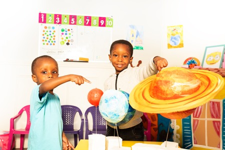 Two boys in early development class show planets