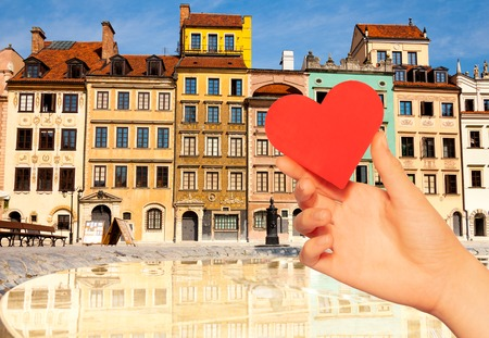 Hand hold red heart over Warsaw, Poland old town