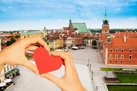 Hand halten rotes Herz über Schlossplatz in Warschau
