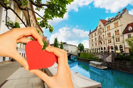Hand hold red heart over Ljubljana river, Slovenia