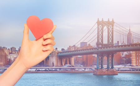 Hand hold red heart over Brooklyn Bridge New York