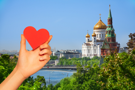 Hand hold red heart over Moscow Christ Cathedral