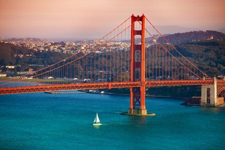 Yacht passing under Golden Gate Bridge at sunset