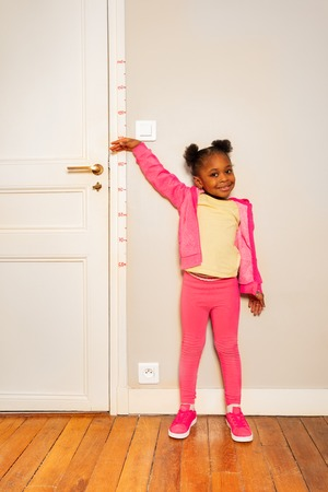 Little girl over scale on wall measure height