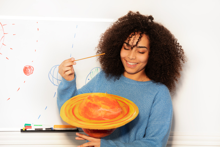 Student African girl showing Saturn planet ng