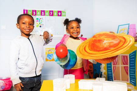 Grupo de niños juegan con planetas del sistema solar.