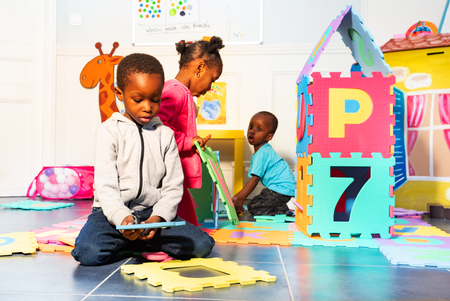 Group of kids play with letter, numbers in class