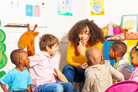 Enseignant à la maternelle lisant un livre aux enfants