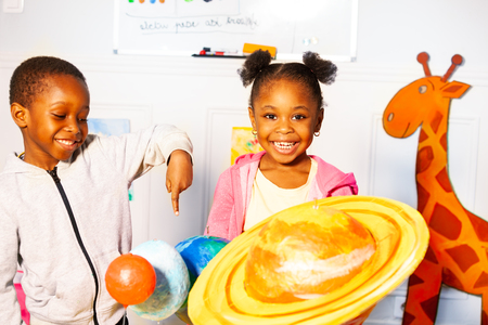 Small black girl with boy learn play planet models
