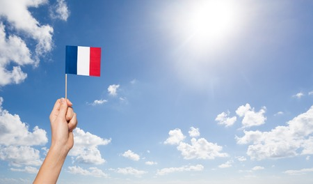 Womans hand holding French flag over the flagpole Фото со стока