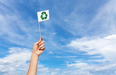 Recycle symbol flag in womans hand against sky