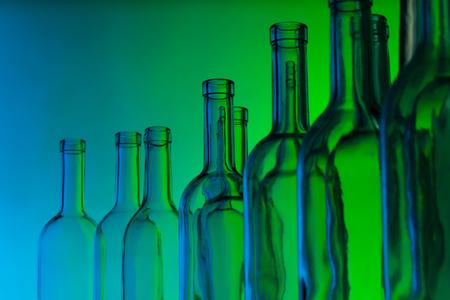Glass wine bottle necks on green background Imagens